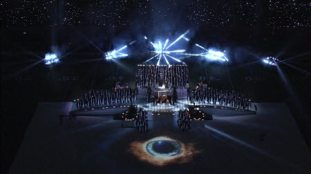 As the song begins, a huge eye pupil is displayed before the stage, hinting to the Illuminá-influence of this spiritual performance.
